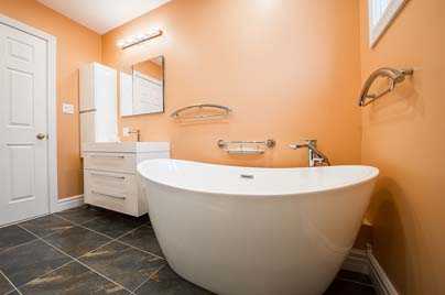 A new bathroom renovation completed in Bondi NSW with orange walls and a big free standing bathtub