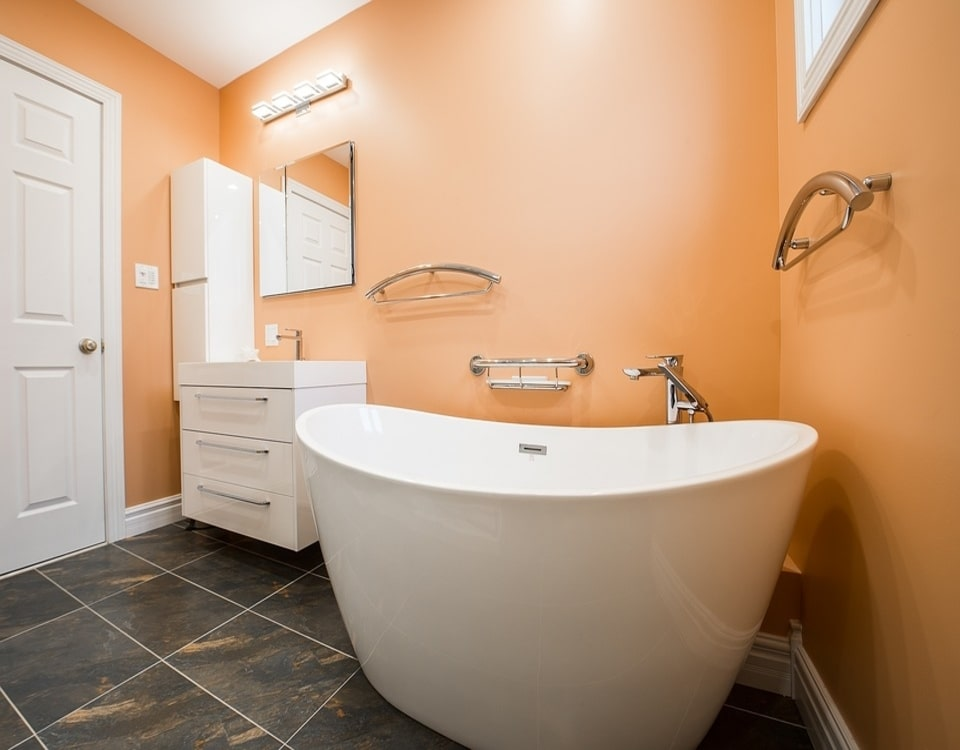 A fresh bathroom renovation in Sydney with bright orange walls and a big white bath tub