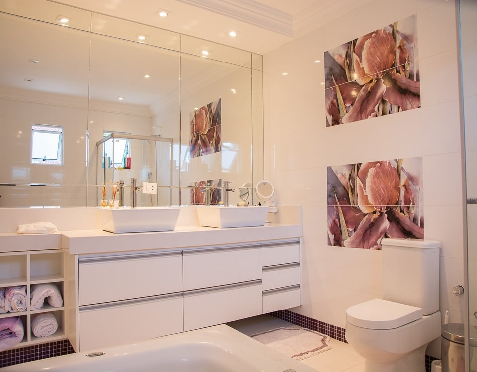 A new bathroom renovated with big mirror on the wall and 2 floral paintings
