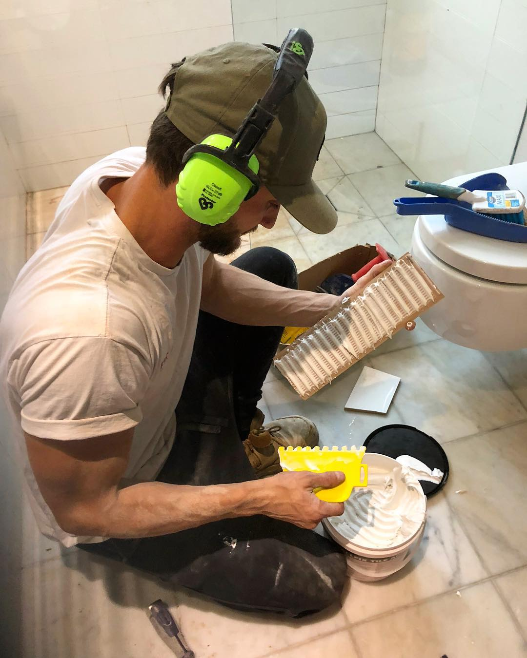 A worker of Pro Projects adding glue to tiles in a bathroom in Bankstown Sydney