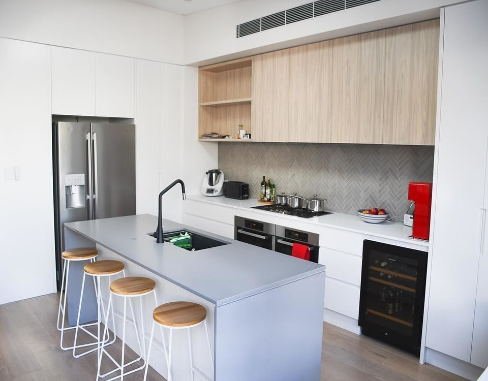 A white renovated kitchen in C with Bondi 2034 stools under a kitchen bench