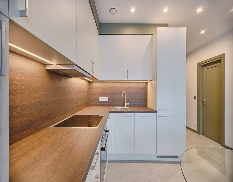A fresh renovated kitchen with evenly spaced downlights shining down