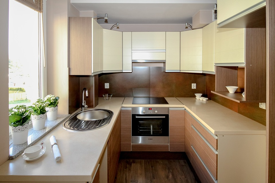 An older style kitchen remodel with yellow bench tops and matching cabinets