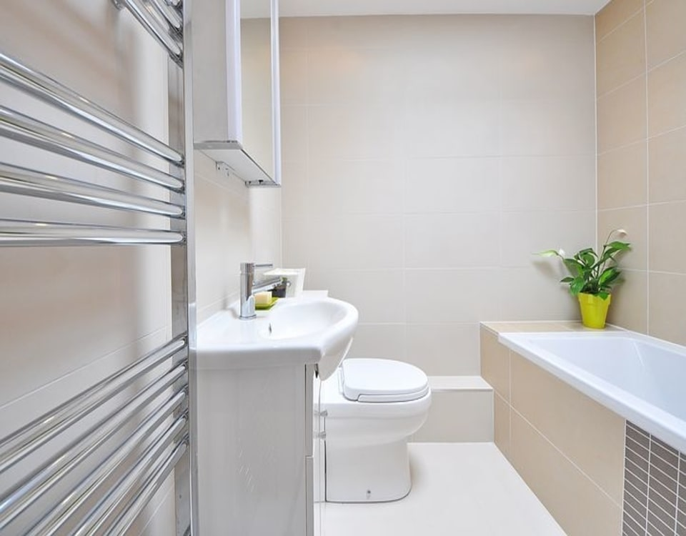 A white renovated bathroom with cream tiles in Newtown, Sydney